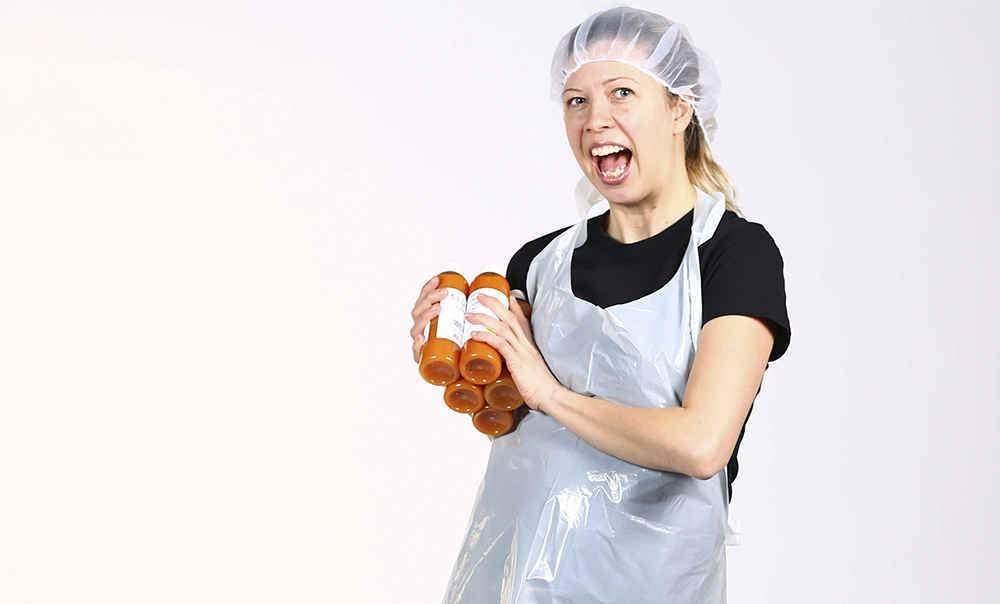 Julie ifoert friskpresningstoej med gulerod chilli Slowjuice i haenden paa hvid baggrund